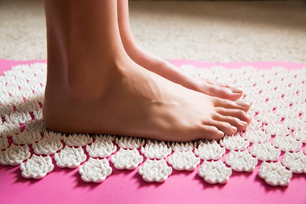 pieds sur tapis d'acupression